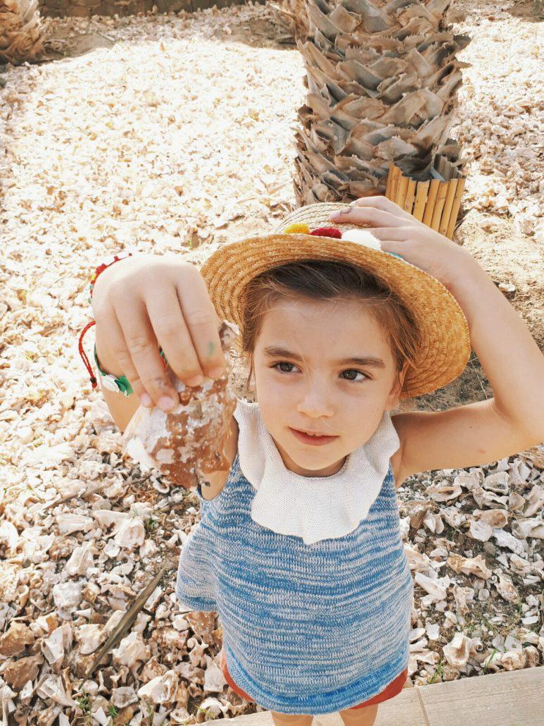 bambina raccoglie conchiglie a capo verde