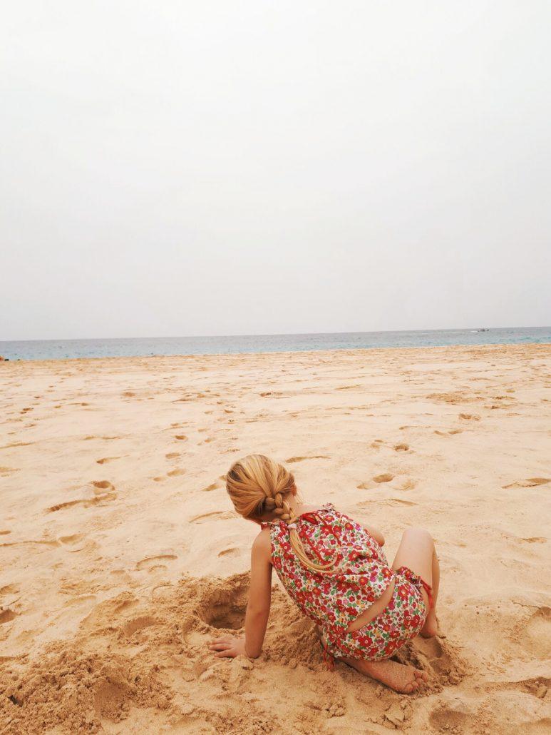 bambina gioca con la abbia nella spiaggia di sal capo a verde
