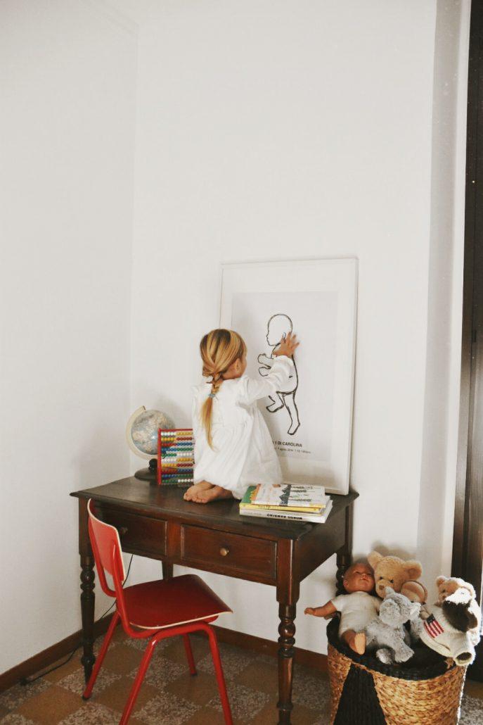 bambina osserva suo ritratto in scala idee nascita neonato