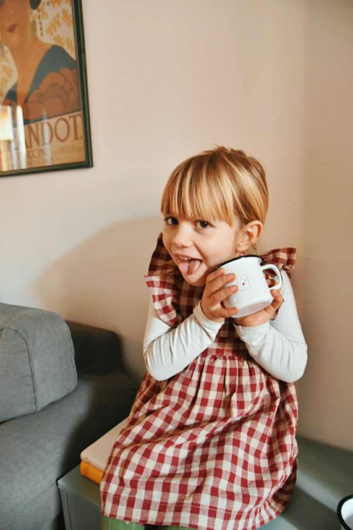 bambina con tazza in latta smaltata