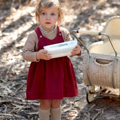 bambina con vestito salopette bordeaux